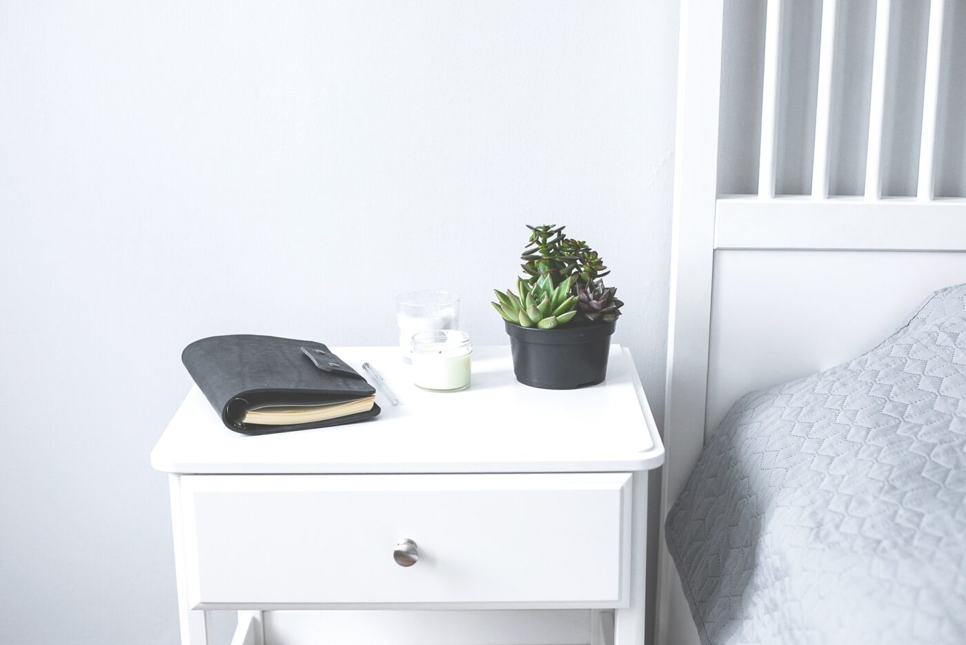 Tiny succulents, candles and black notebook on bedside table in the bedroom in scandinavian style home. Scandinavian interior in gray and white colors