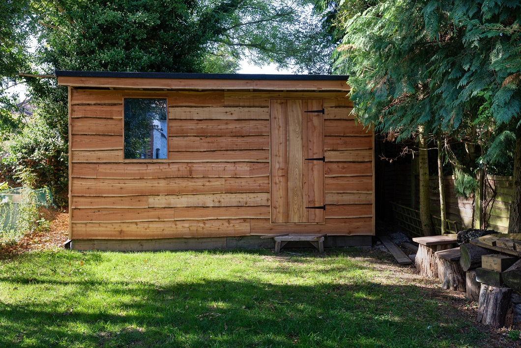 Rustic waney edge wooden garden shed surrounded by mature green trees.