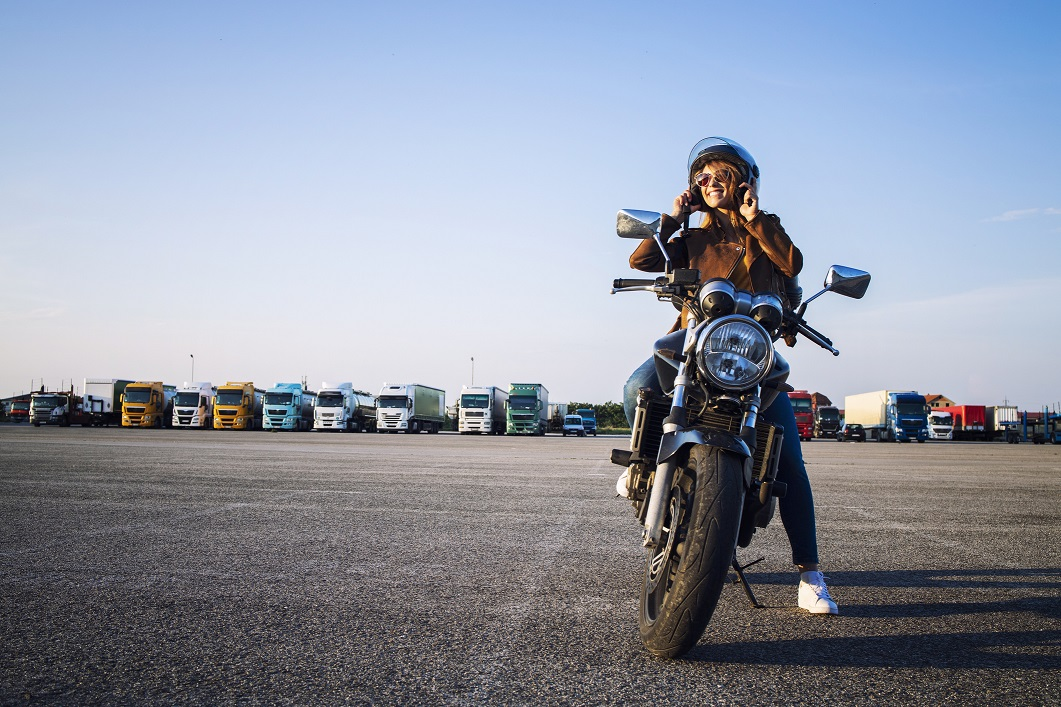 Woman in leather jacket sitting on retro style motorcycle